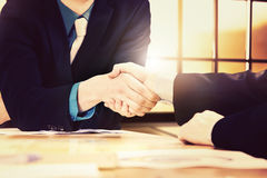 Handshake above table with bright sunlight. Two businessman shake hands above conference room table Stock Photography