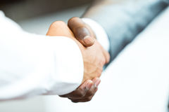 Handshake between african and a caucasian man Stock Photos