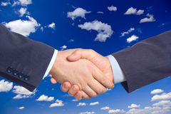 Handshake against clouds Royalty Free Stock Photography