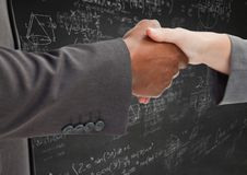 Handshake against grey wall with math doodles royalty free stock photography