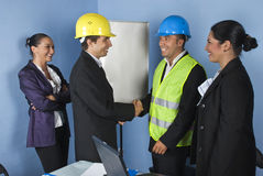 Handshake architects  happy team. Two architect men giving  hand shakes and  engineer woman laughing together and having fun,check out  Workers and tools Stock Photos