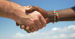 Handshake as symbol of international friendship. Close-up shot of Caucasian and Afro-American men shaking hands on blue sky background. International friendly stock video footage
