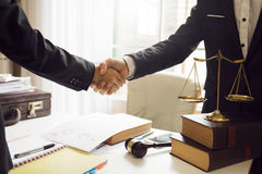 Handshake between attorneys and clients after agreeing. To enter into a contract for a court case. In the hope of victory over legal fighters royalty free stock photos