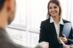 Handshake attraente sorridente della donna di affari con l'uomo d'affari dopo la conversazione piacevole, buone relazioni Foto di fotografia stock libera da diritti
