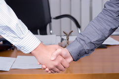Handshake on background of a table. Close-up Stock Images