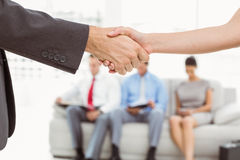 Handshake besides people waiting for interview Stock Photo