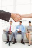 Handshake besides people waiting for interview Royalty Free Stock Images