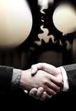 Handshake with black gears background Royalty Free Stock Photo
