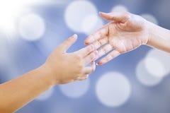 Handshake on blue defocused lights Royalty Free Stock Photography