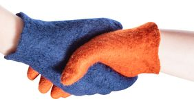 Handshake of blue and orange gloved hands stock photography