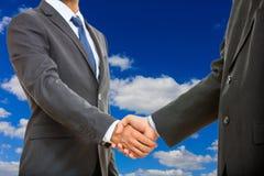 Handshake on blue sky background Stock Photography