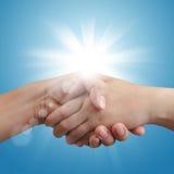 Handshake on blue sky and sunlight Royalty Free Stock Photos