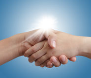 Handshake on blue sky and sunlight Stock Photos