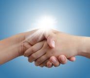 Handshake on blue sky and sunlight Stock Photos