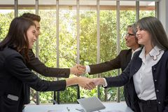 Handshake. Business associate shaking hands in office. Two businessmen shaking hands in office. asian. The office. presentation. With computer. asian people stock photography