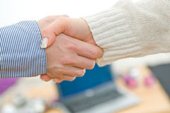 Handshake in business environment. A man and a woman shaking hands to confirm a mutual deal Stock Photography