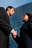 Handshake business man and woman modern building. Handshake business man and woman on modern building background stock image