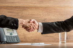 Handshake of business  partners above a written agreement Stock Photography