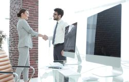 Handshake of business partners on background of blank screens Stock Photography
