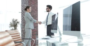 Handshake of business partners on background of blank screens Royalty Free Stock Image