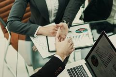 Handshake of business partners on the background of financial documentation. Closeup of handshake of business partners in the workplace in the office Stock Image