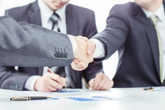 Handshake of business partners on the background of a lawyer and financial documents. Closeup of handshake of business partners on the background of a lawyer and Stock Photography