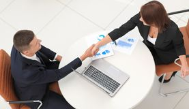 Handshake business partners after the discussion of financial documents. The concept of partnership Royalty Free Stock Photo