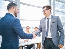 Handshake of business partners. After discussion of the financial reports, their team on background royalty free stock image