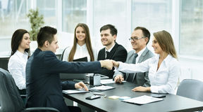 Handshake business partners at a meeting in creative office on the background of business team stock photography