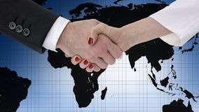 Handshake. Business partners shaking hands over map of the world Stock Photos