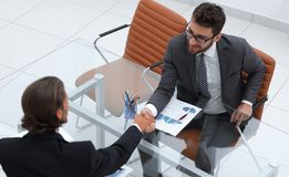 Handshake of business partners sitting at their Desk. Photo with copy space Royalty Free Stock Photo