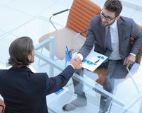 Handshake of business partners sitting at their Desk. Photo with copy space Royalty Free Stock Images