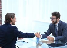Handshake of business partners sitting at their Desk Royalty Free Stock Photography