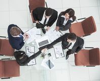 Handshake of business partners before the talks near the desktop in. Top view - handshake of business partners before the talks near the desktop in a modern Royalty Free Stock Images