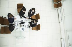 Handshake of business partners before the talks near the desktop in. Top view - handshake of business partners before the talks near the desktop in a modern Stock Images