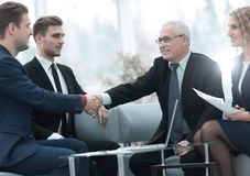 Partners concluding deal and shaking hands in the presence of team members Stock Photos