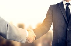 Handshake and business people concept. Two men shaking hands over sunny sity background. Partnership.  Stock Photos