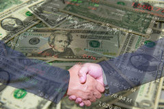 Handshake and business people concepts. Two men shaking hands isolated on Dollar Banknote background. Close-up image of handshake between two business man Royalty Free Stock Images