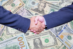 Handshake and business people concepts. Two men shaking hands  on Dollar Banknote background. Close-up image of handshake between two business man Royalty Free Stock Images