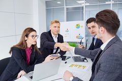 Handshake business people. A group of businessmen at desk in  mo Royalty Free Stock Images