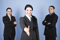 Handshake business woman and her team. Three business people team standing and smiling for you with a businesswoman in front of image giving hand shake,check Stock Images