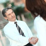 Handshake of a businessman and business women standing in the center of the modern office stock photos