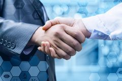 Handshake of a businessman and a doctor . Handshake of a businessman and a doctor on blurred background stock photos