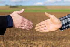 Handshake between businessman and farmer Stock Photo