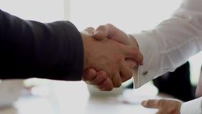 Handshake of businessmen having deal. Big light office. Business partners making a deal in big office. Handshake of two businessmen closed-up view. Partnership stock video