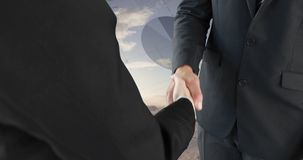 Handshake between businessmen 4k. Close up of a handshake between businessmen with a background of a wide open field. Digital animation of graphs an statistics stock video footage