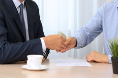 Handshake of businessmen with money. Blue background behind Royalty Free Stock Photo