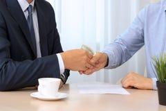 Handshake of businessmen with money. Blue background behind Royalty Free Stock Photo