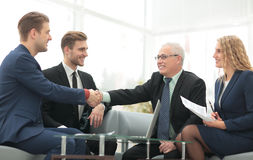 Handshake between businesspeople in a stylish office  in the bac Stock Photos