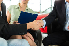 Handshake at car dealership with auto Royalty Free Stock Photos